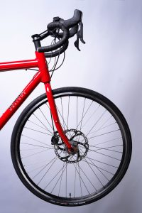 Closeup of red Tailwind electric assist tandem front handlebars, fork and wheel